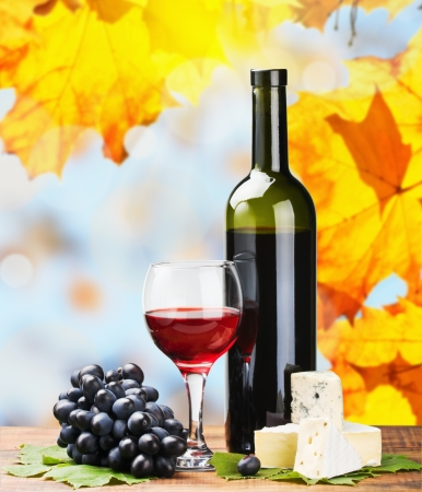 bottle, glass of red wine and assorted cheeses on a background of autumn leaves photo