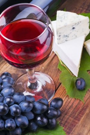 glass of red wine and grapes are ripe. Focus on a glass of wine. photo