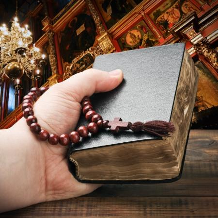różaniec: ludzkie ręce trzyma Biblię i modli się z różańcem Zdjęcie Seryjne