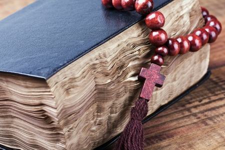 wooden rosary lying on a closed Bible photo