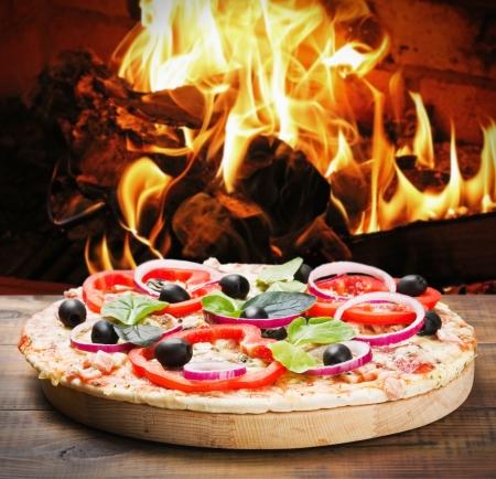 pizza met ham en kaas bereid op het vuur in de kachel