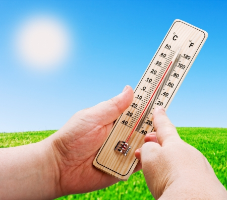 houten thermometer in de hand op een achtergrond van een felle zon Stockfoto