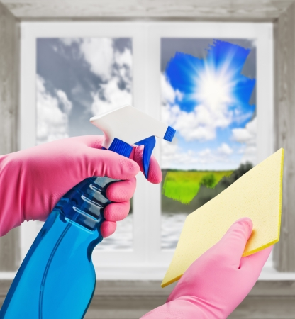 window cleaner: hands in pink gloves with means clears the dirt from the window