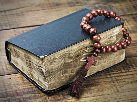 wooden rosary and the Bible on the table photo