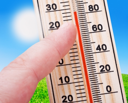 Thermometer in hand, shows a strong heat of the summer landscape background photo
