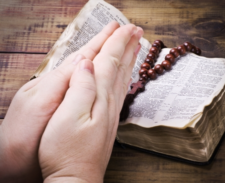 credo: human hands holding the Bible and praying with a rosary