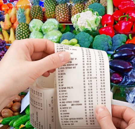 hand holds the check from supermarket against vegetables and fruit photo