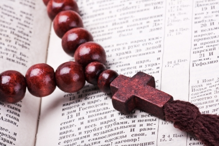 rosary with a wooden cross lying on open Bible photo
