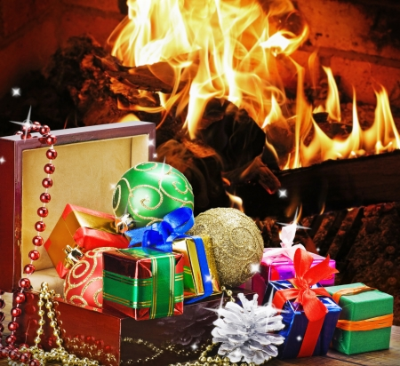 Christmas toys and decorations in wooden box on the background of the fire in the fireplace Stock Photo - 15988822
