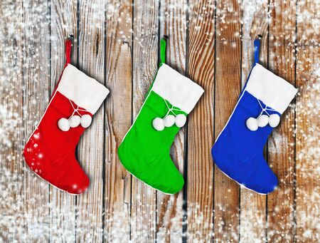 Christmas colored socks hanging on a wooden wall Stock Photo - 16353475