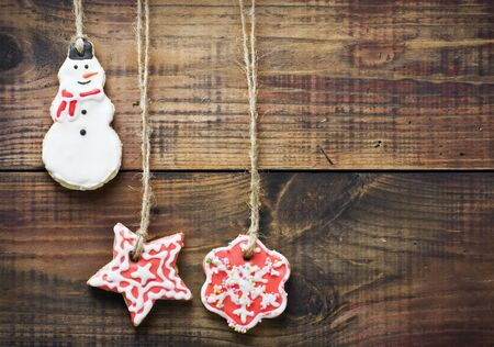 christmas gingerbread cookies hanging over wooden background photo