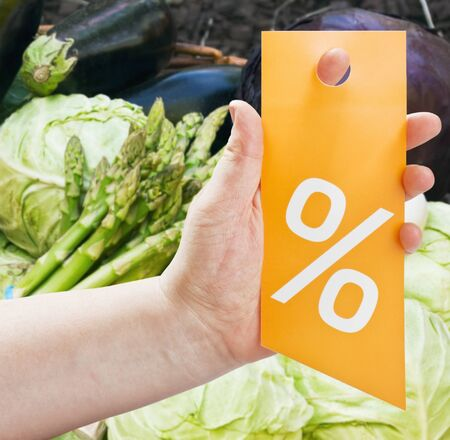 hand holding a card for discounts against products in the store Stock Photo - 16451552
