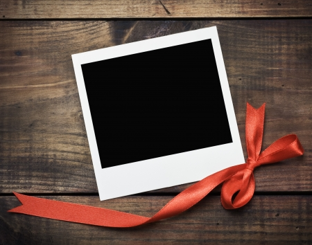 romantic picture: photo frame with a red bow on a wooden background