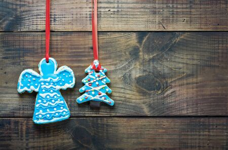 Gingerbread cookies hanging over wooden background  photo