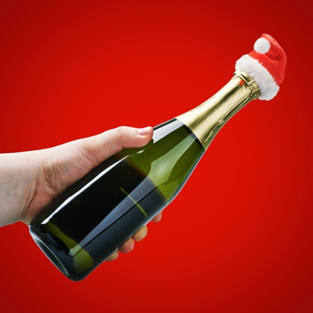 hand holding a champagne bottle in a Christmas decoration santa clothes on a bordo background  photo