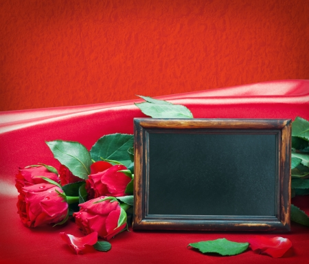 red roses and blackboard with space for text on a red background  photo