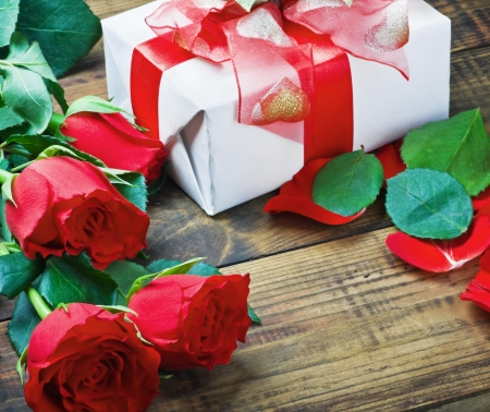 red roses and holiday gift on a wooden table photo