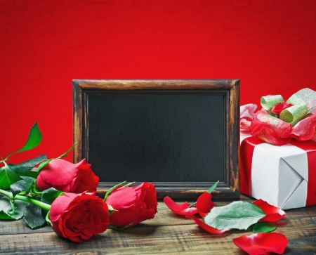 Red roses and gift for Valentine's Day or a birthday on a red background photo