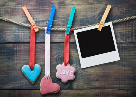 Valentine cookies and picture frame hanging on a rope on a wooden background photo