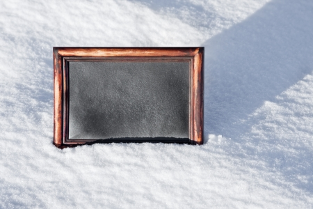 black wooden board with space for text on white snow photo