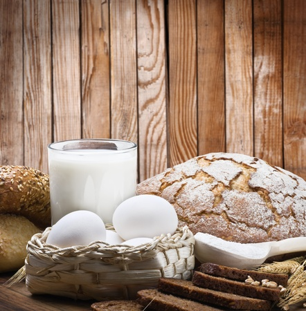 fresh baked bread and ingredients on a wooden fence background photo