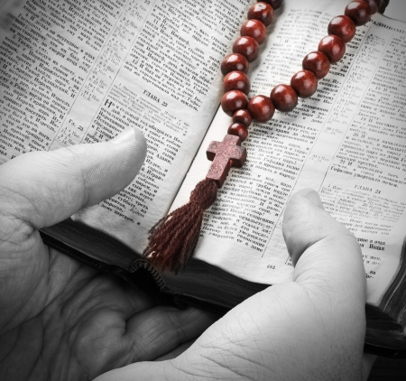 human hands holding the Bible and praying with a rosary. Bible in Russian.  photo