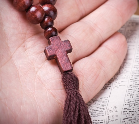 wooden rosary and a Christian cross in his hand against the Bible photo