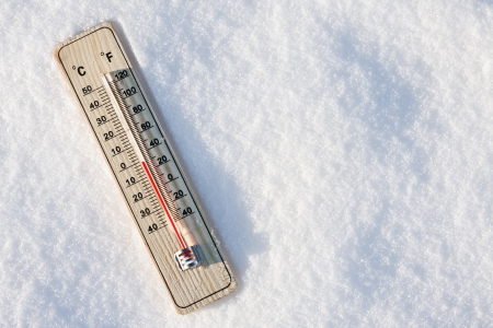 wooden thermometer in the snow with zero temperature photo