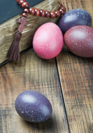 dyed Easter eggs and religious Christian symbols on a wooden table photo