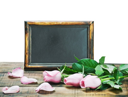 black board and pink roses on a white background photo