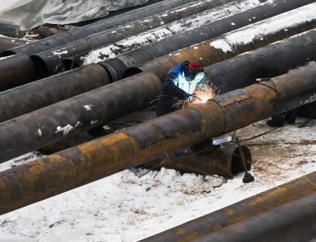 welder welds metal pipes in winter Stock Photo - 18588140