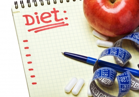 notebook with diet plan and a measuring tape with pills photo