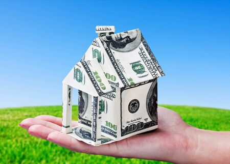 House made of money in hand on background of green field photo