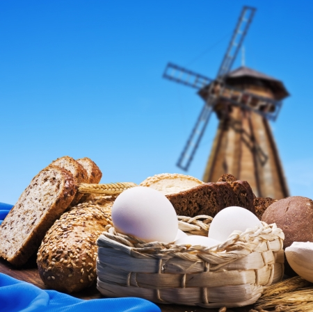 fresh bread on the background of the old wooden mill photo