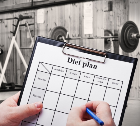 diet plan against trainers and sports equipment photo