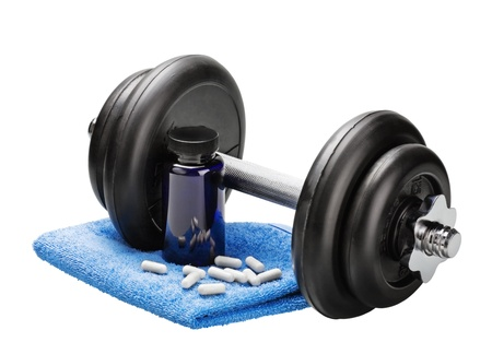 enhancing: Dumbbells and pills with a towel on white background