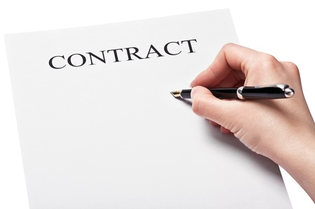 hand with pen signing a contract isolated on white background photo