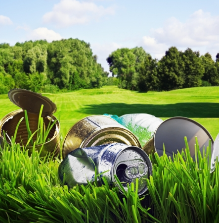 old aluminum and tin cans on a background of green field photo