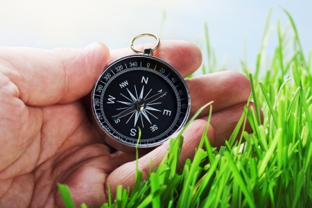 compass in hand on a background of green grass