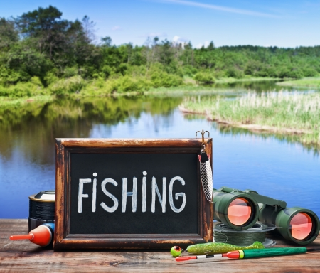 fishing tackle and a blackboard on a background of lake photo