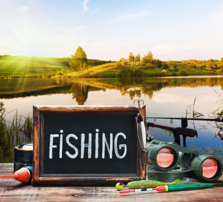fishing tackle and a blackboard on a background of lake at sunset