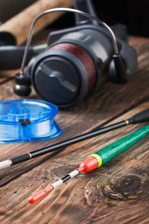 fishing tackle on a wooden table. Focus on the float. photo