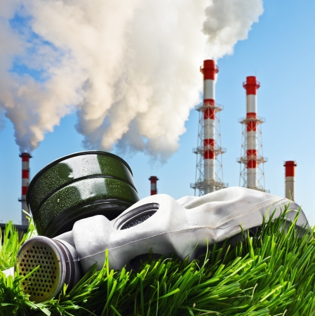 old gas mask on a green grass on a background of smoking chimneys polluting the planet photo