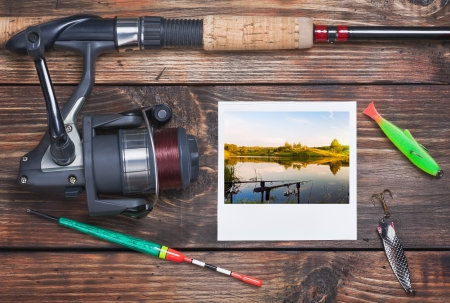 fishing tackle and a photo of successful fishing on the table photo