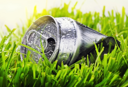 crumpled aluminum can on a green grass (pollution ecology of the planet) photo
