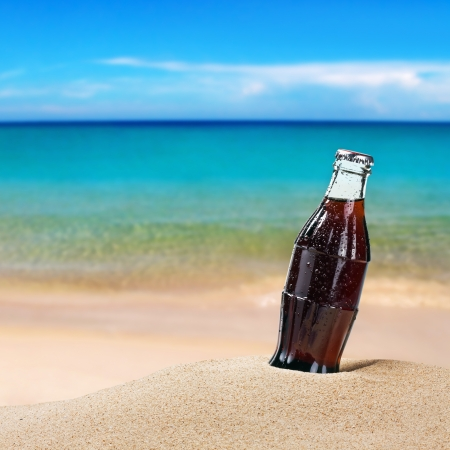 sweating bottle of cola on the sand on the beach background