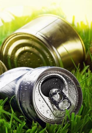 crushed aluminum cans: basura en la hierba contra el cielo soleado. conceptual sobre el tema de la contaminaci�n ambiental Foto de archivo
