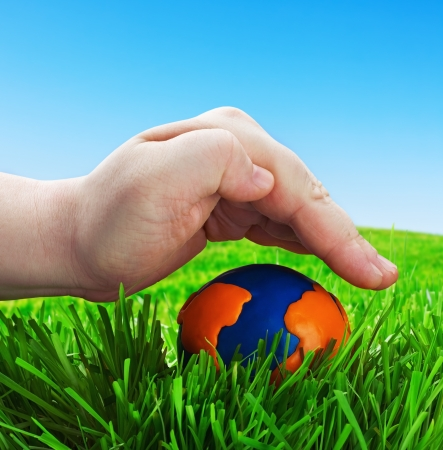 conceived: mans hand on a globe made of plasticine. Conceived on the protection of the environment and the fragility of our planet. Stock Photo