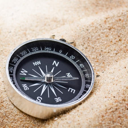 magnetic north: compass in the sand lit by the rays of the sun