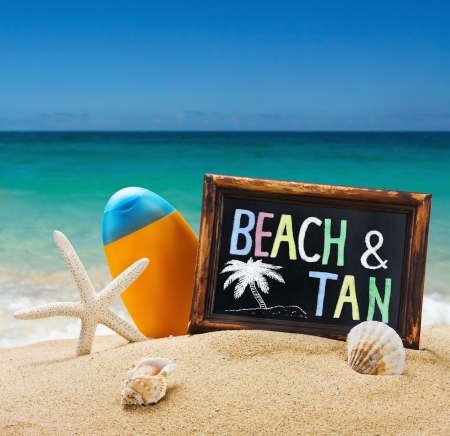 blackboard with the word beach and tan on the sea sand photo